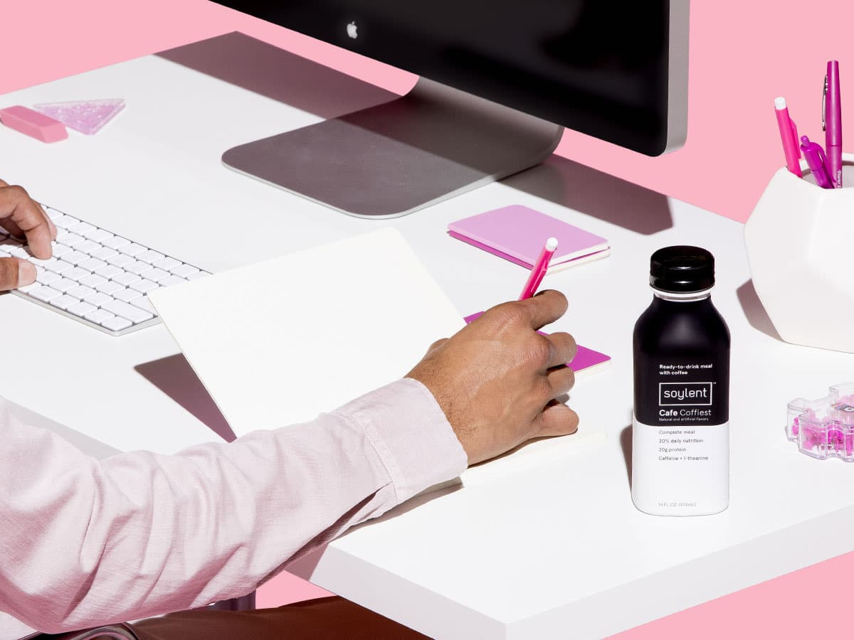 A man working at a desk with a bottle of Soylent Cafe Coffiest next to him.