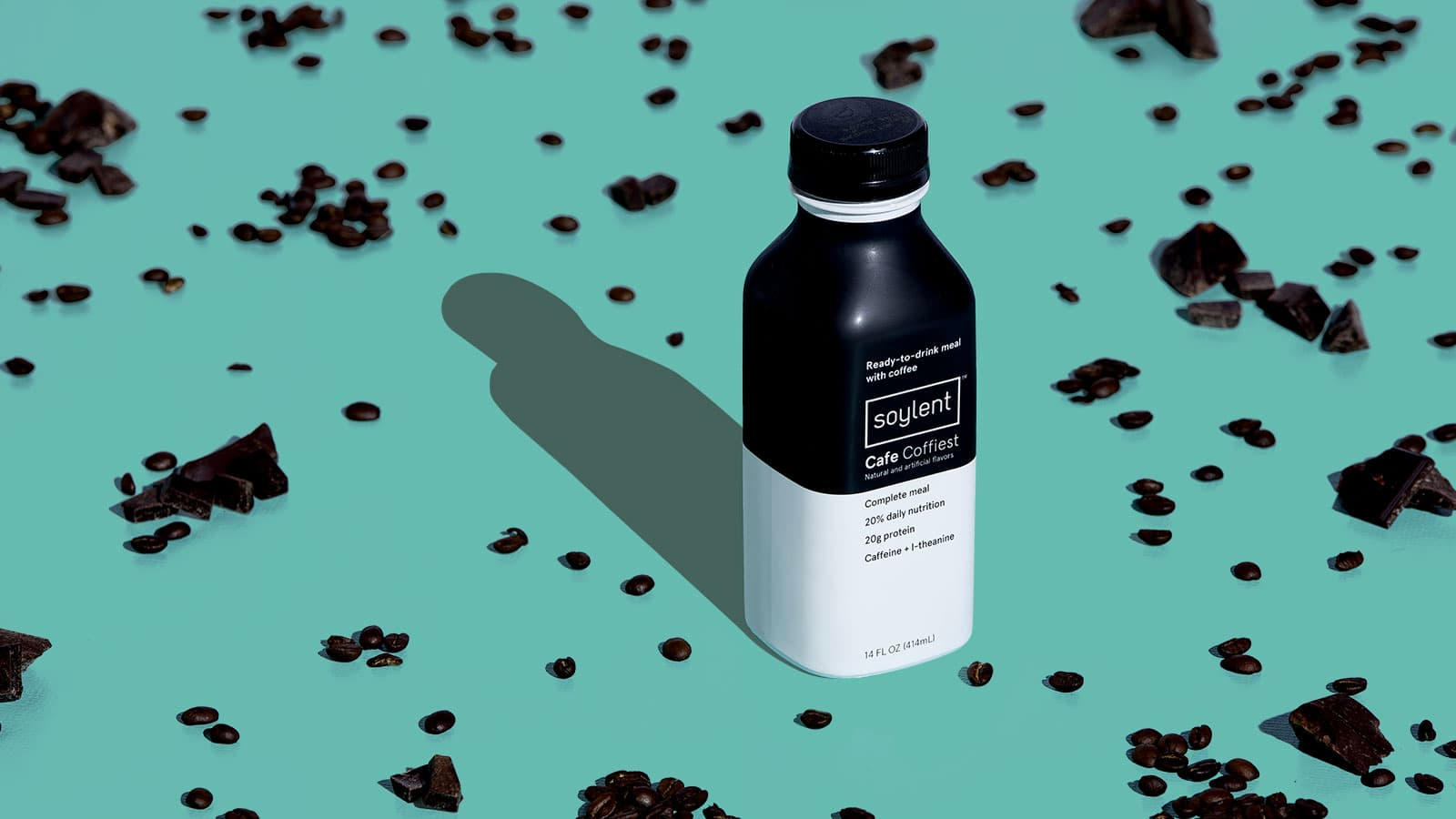 A bottle of Soylent Cafe Coffiest surrounded by coffee beans and chocolate chunks.