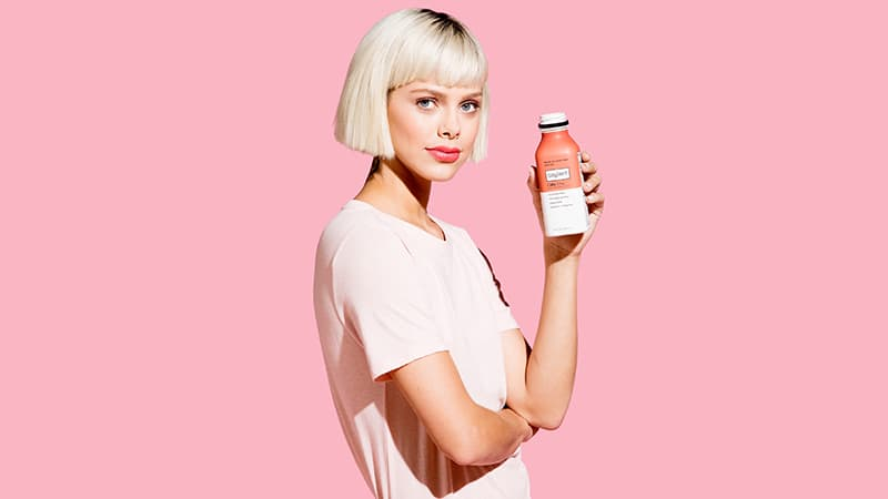 Woman holding a bottle of Soylent Cafe Chai.