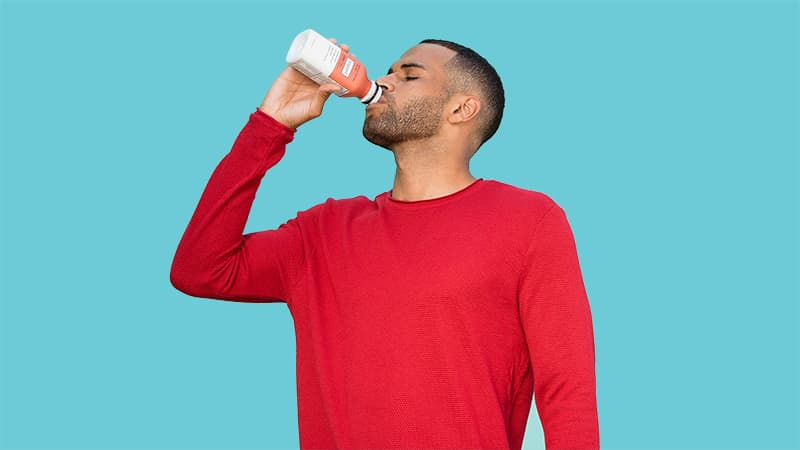 Man drinking a bottle of Soylent Cafe Chai.