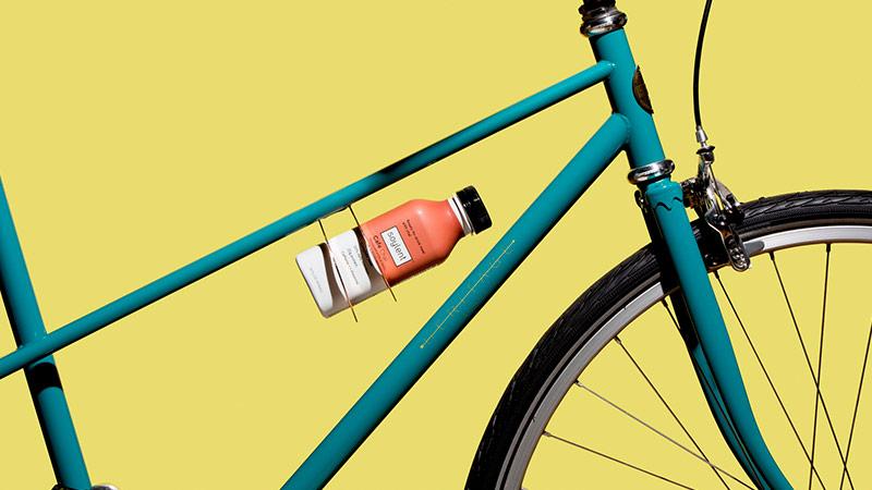 A bottle of Soylent Cafe Coffiest in a bike frame mounted bottle holder.
