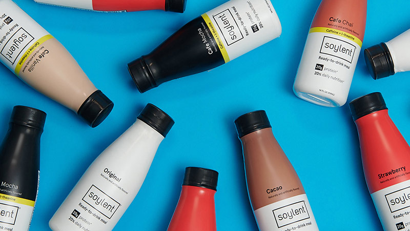 Three empty bottles of Soylent Drink in the shape of a recycling icon.