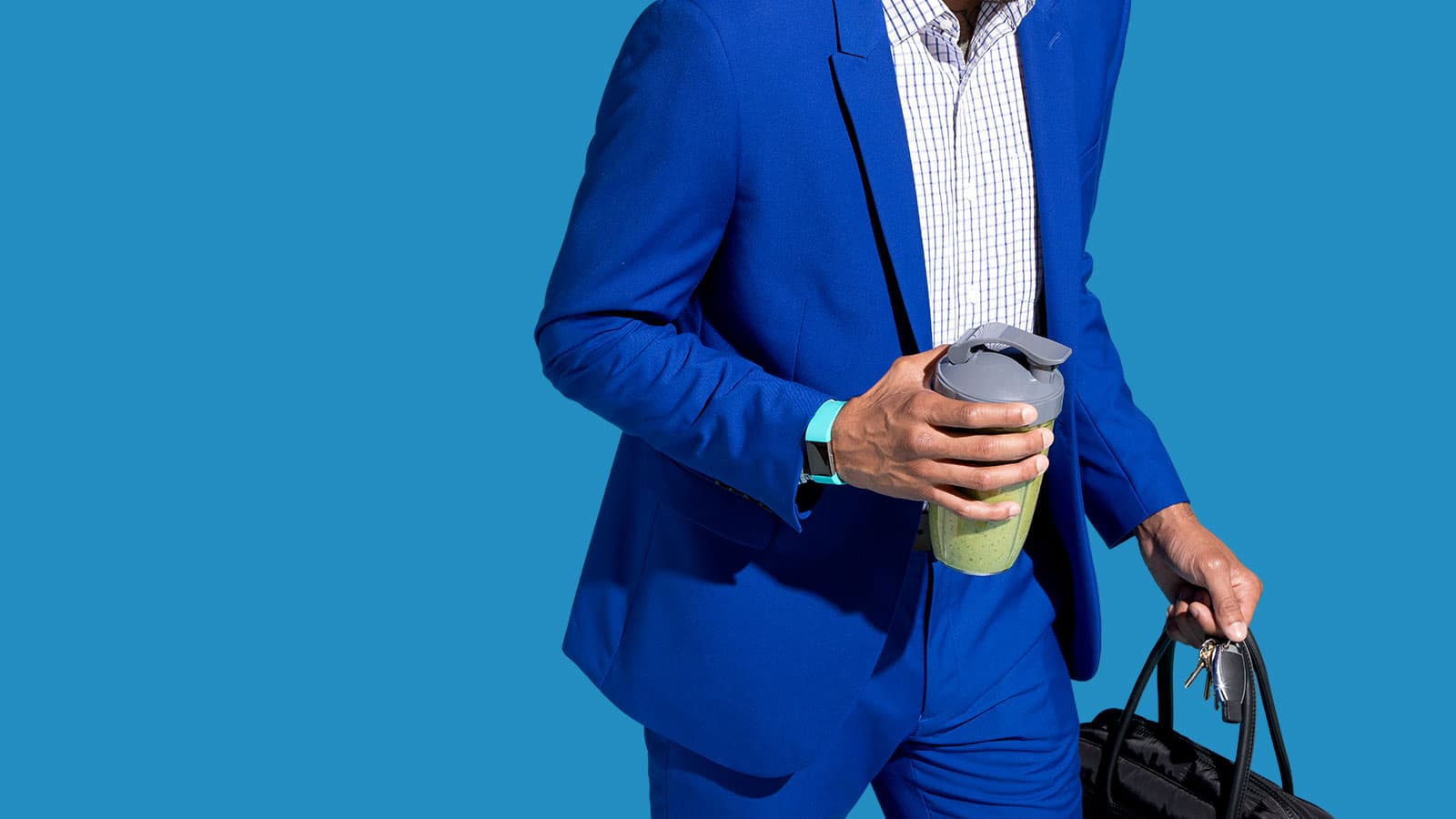A man going to work with a travel cup filled with a Soylent Powder smoothie.