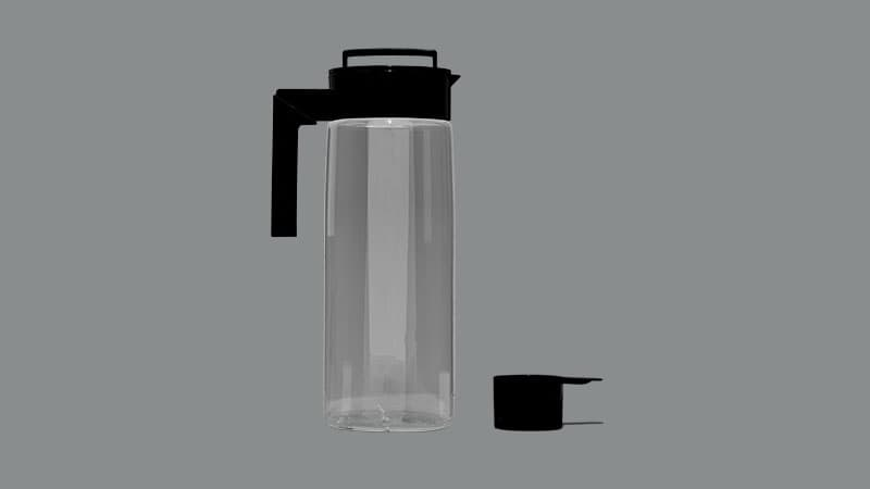 A clear plastic pitcher with black lid and a black plastic measuring scoop.