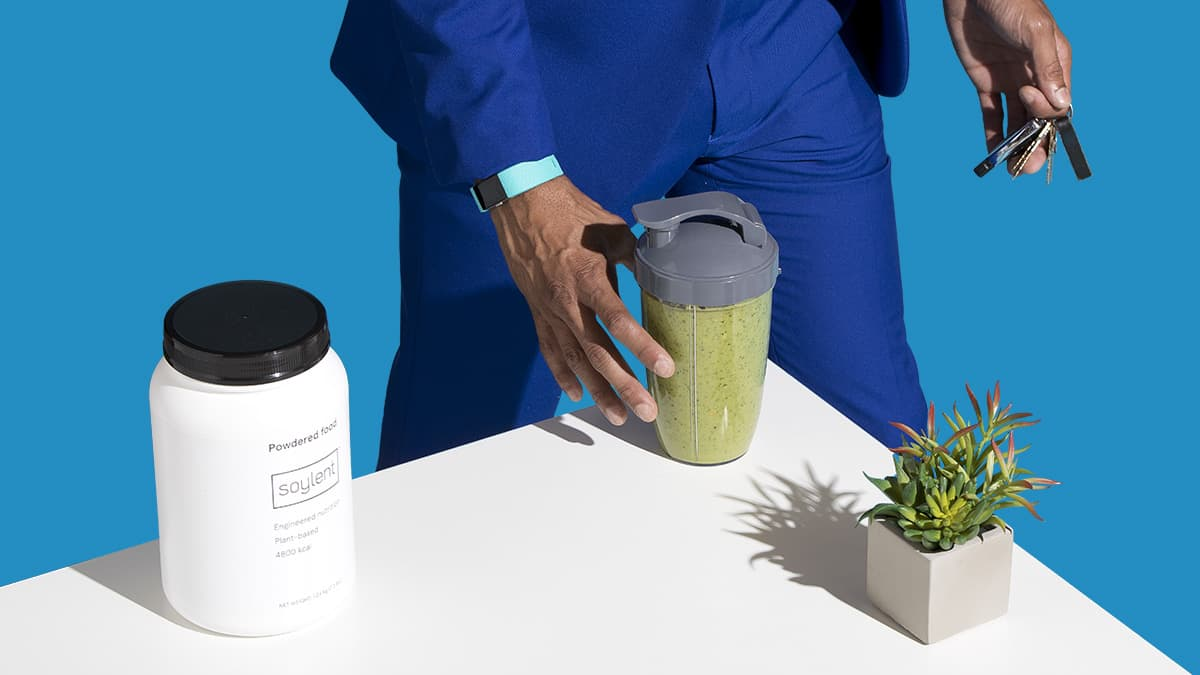 Man grabbing a travel mug filled with a Soylent Powder smoothie from a table with Soylent Powder Tub and small plant.
