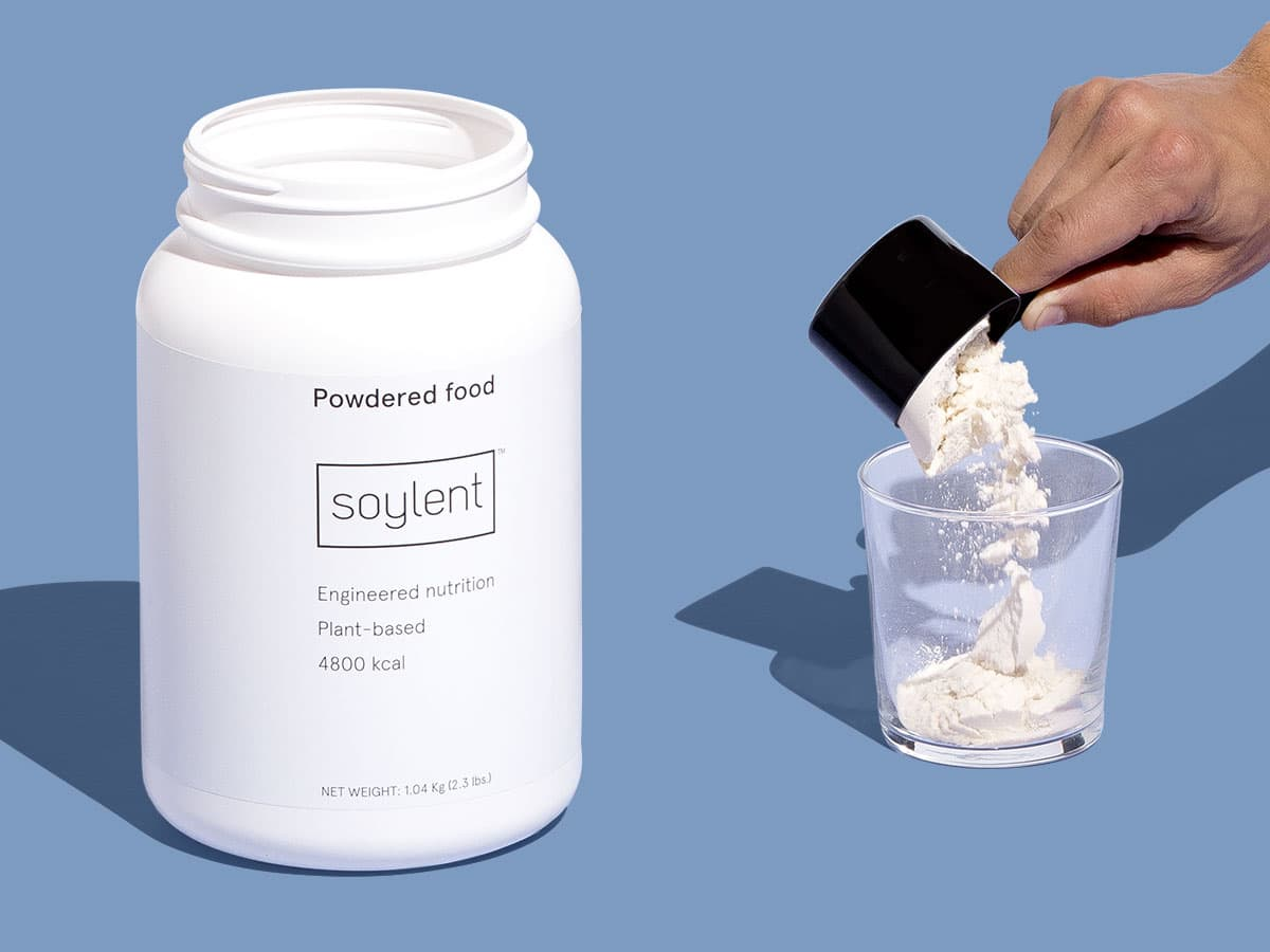 Soylent Powder Tub with hand pouring scoop into glass.