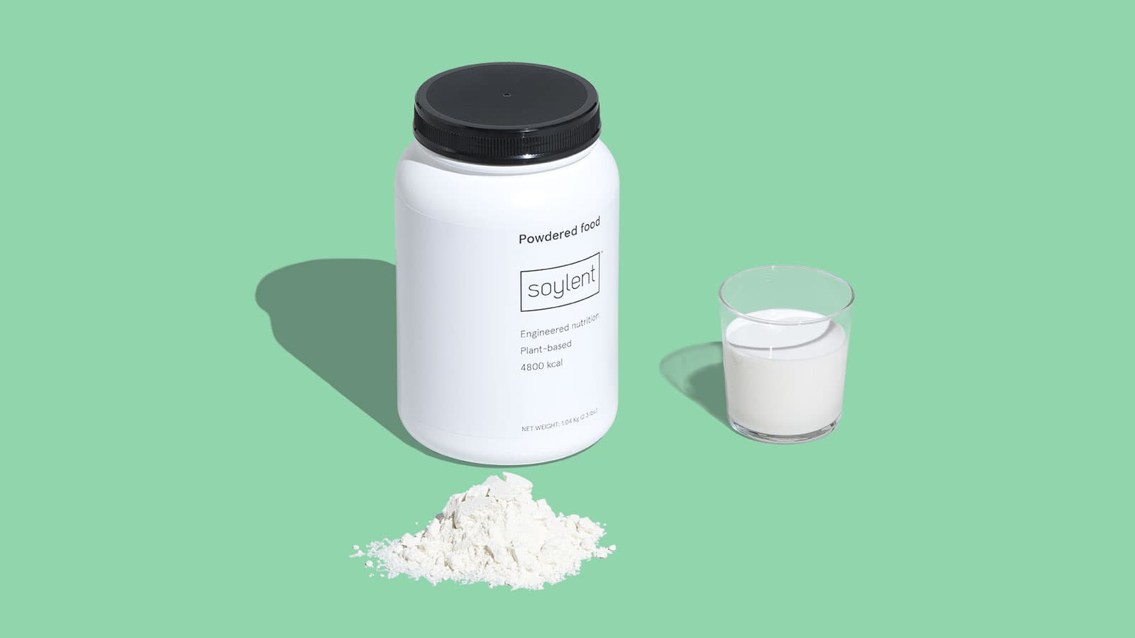 Soylent Powder Tub next to a glass of mixed Soylent Powder and infront of a mound of Soylent Powder.