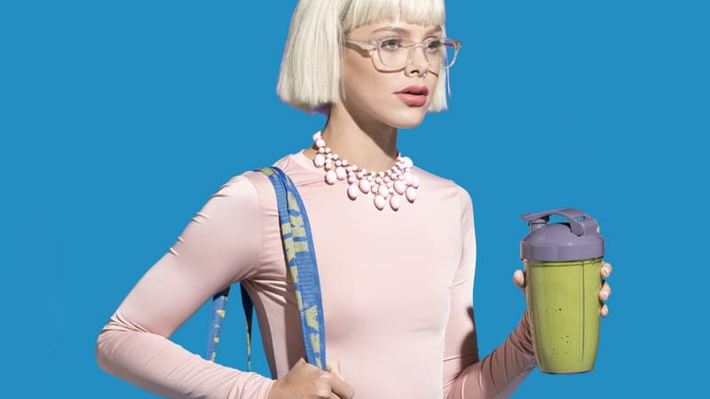 Woman holding a travel mug with a Soylent Powder smoothie.
