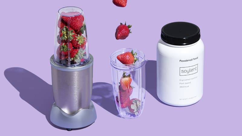 Blender with strawberries next to a Soylent Powder Pouch and a glass of smoothie.